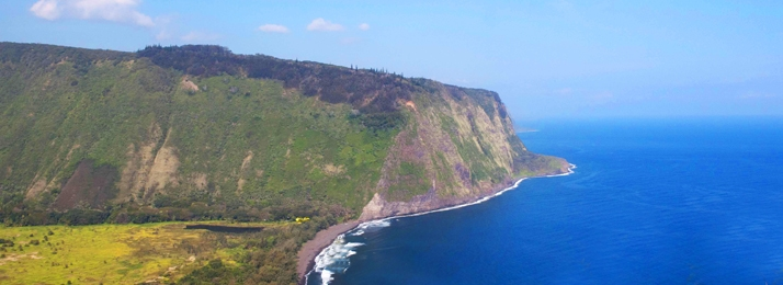 Waipio Valley overlook, vast bright blue ocean colliding with the rich green of the Big Islands coast line