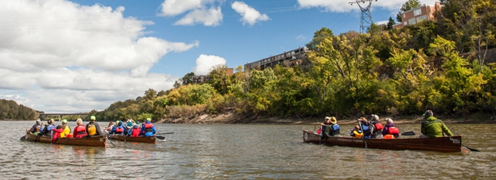several canoes paddling on the Mississippi River