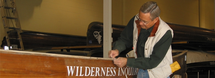 man working on a Wilderness Inquiry voyageur canoe in WI's warwehouse