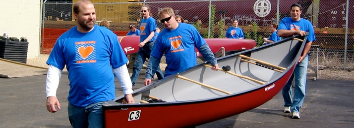three male volunteers wearing matching shirts carrying a canoe in a parking lot