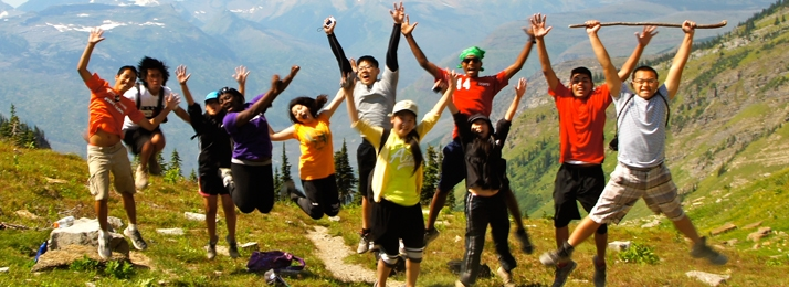 eleven youths jumping in the air on a trail in Glacier National Park
