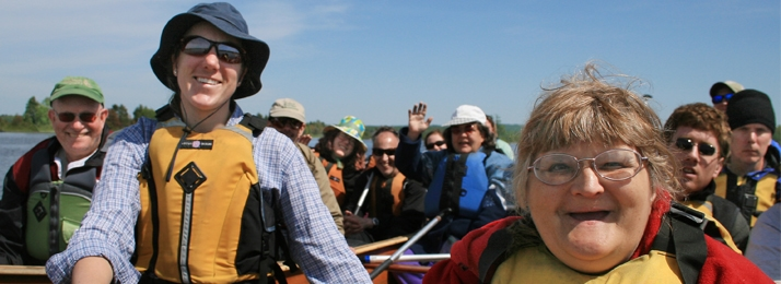 Group paddling in canoes wearing life vest and smiling
