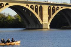voyageur canoe paddling near the Key Bridge on the Potomac River