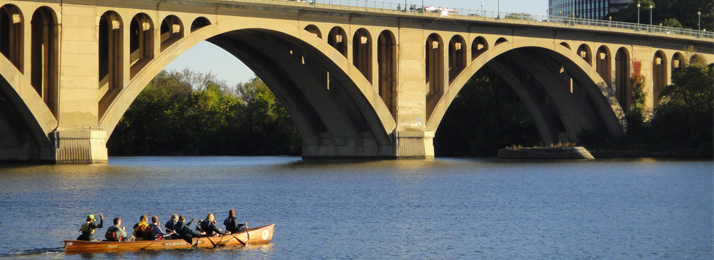 voyageur canoe paddling near the Key Bridge on the Potomac River
