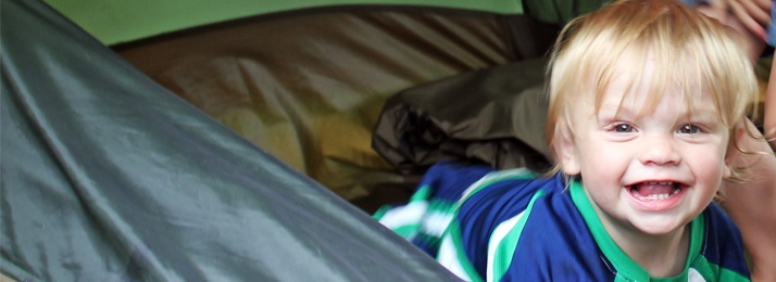 blonde toddler smiling in a tent