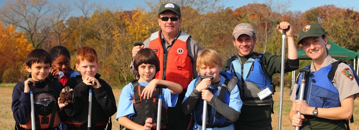 a group of youth with two rangers for the National Parks Service posing with paddles for the camera