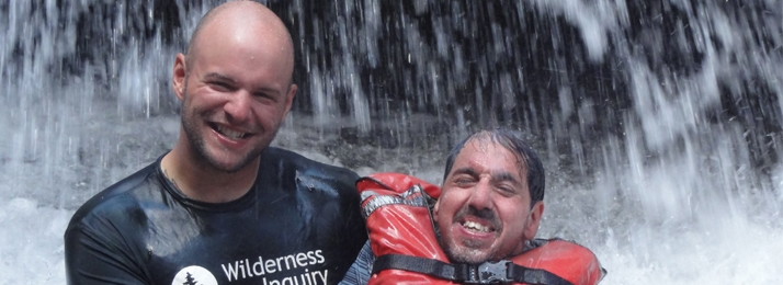 Wilderness Inquiry employee holding up man wearing a life vest in water under a waterfall