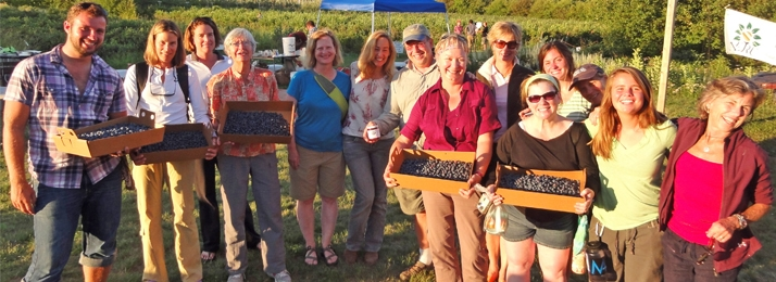 smiling group holding boxes of blueberries at a local farm stand near the Apostle Islands near Bayfield, WI