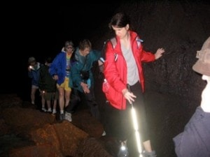 Woman with glowing white cane leading group in lava tubes in Hawaii Volcanoes National Park