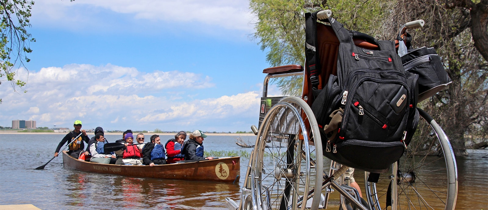 Voyageur canoe with wheelchair on shore