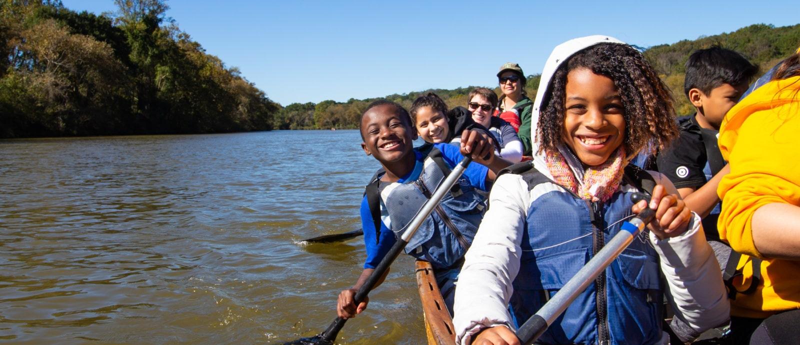 African American children outdoors in Voyageur Canoe with Canoemobile Program.