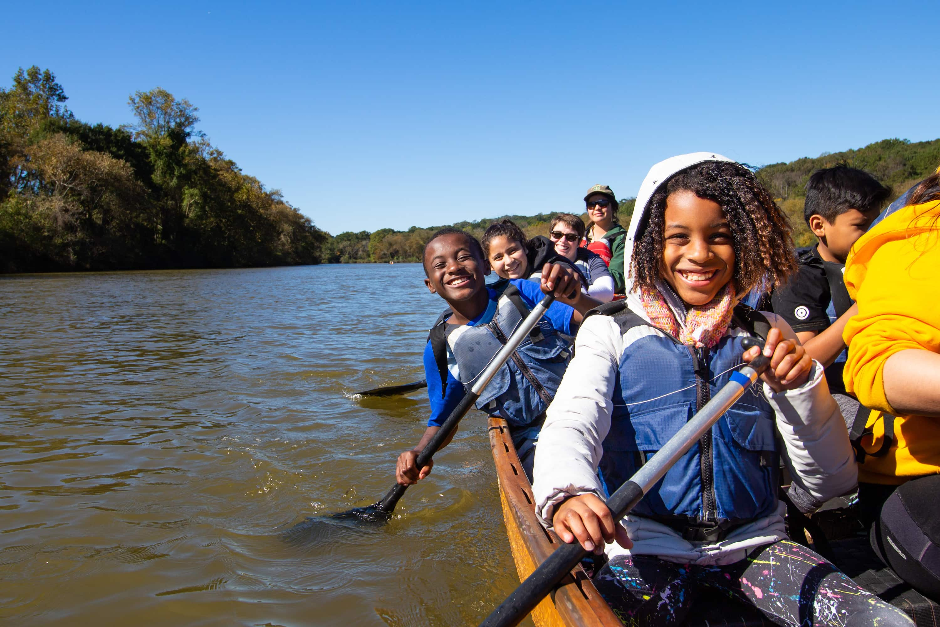 African American children outdoors in Voyageur Canoe with Canoemobile Program.