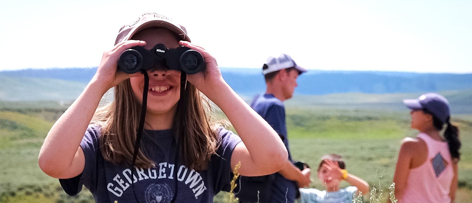 Girl with binoculars on a family trip