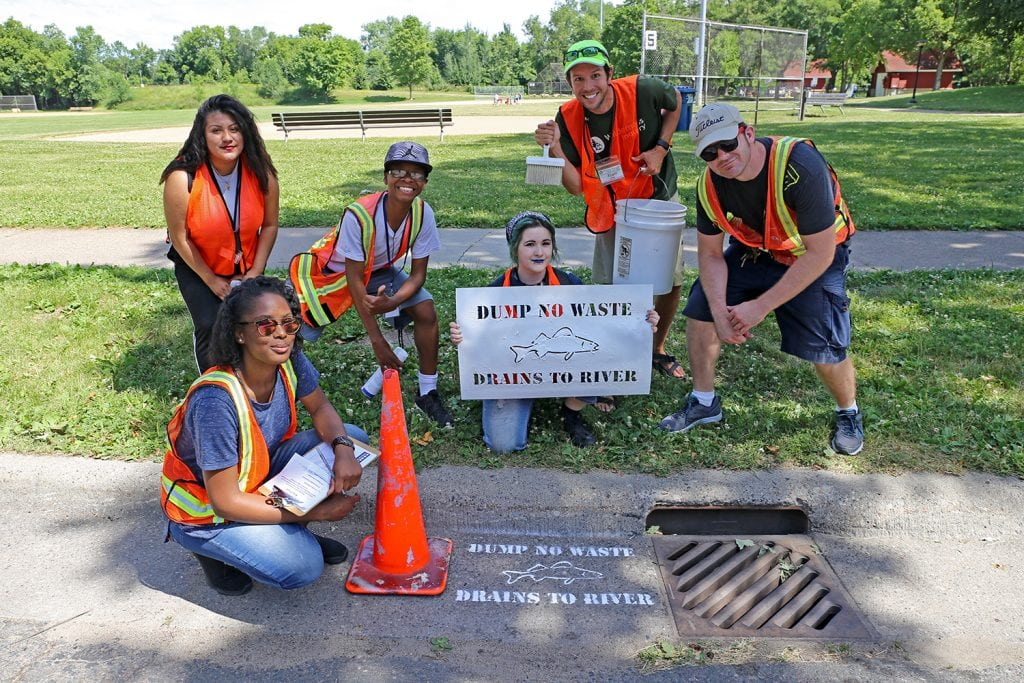 Students with the storm drain warning they stenciled.