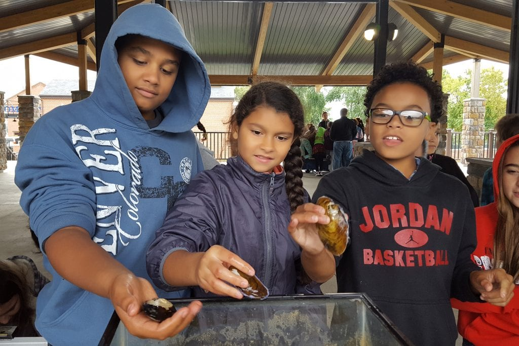 Children check out and hold mussels.