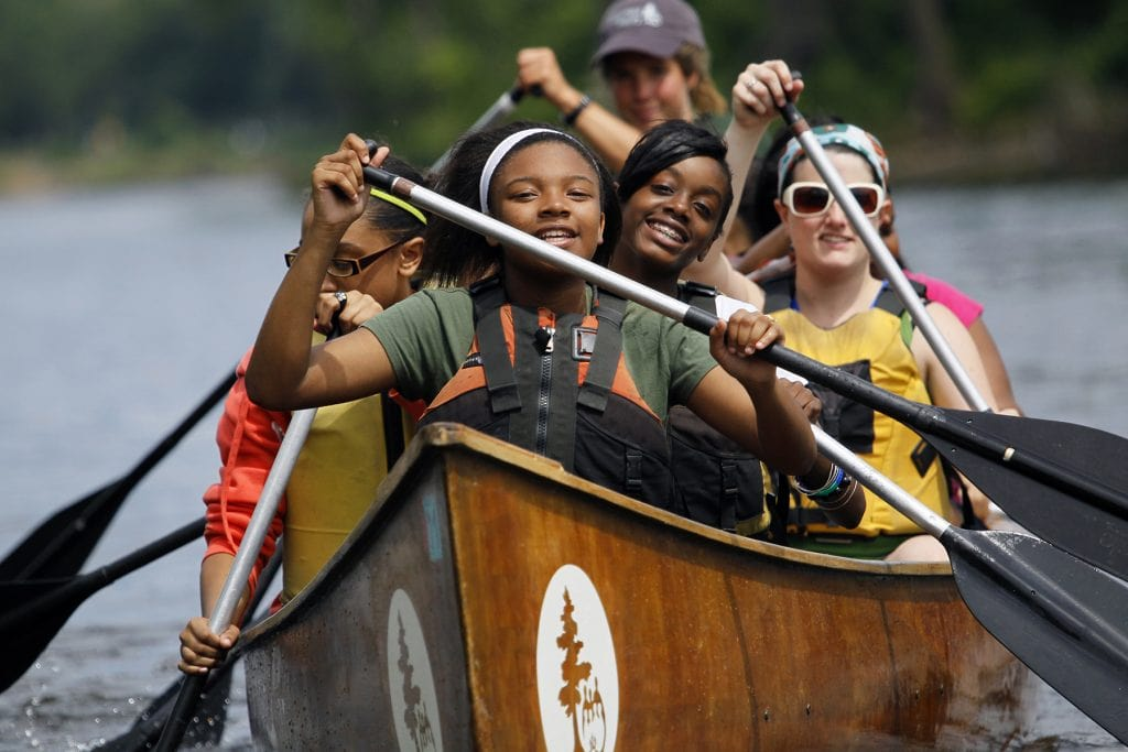 Students paddle a Voyageur canoe