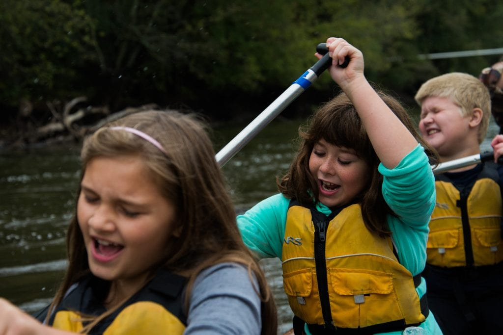 Two young girls chant in rhythm as they paddle.