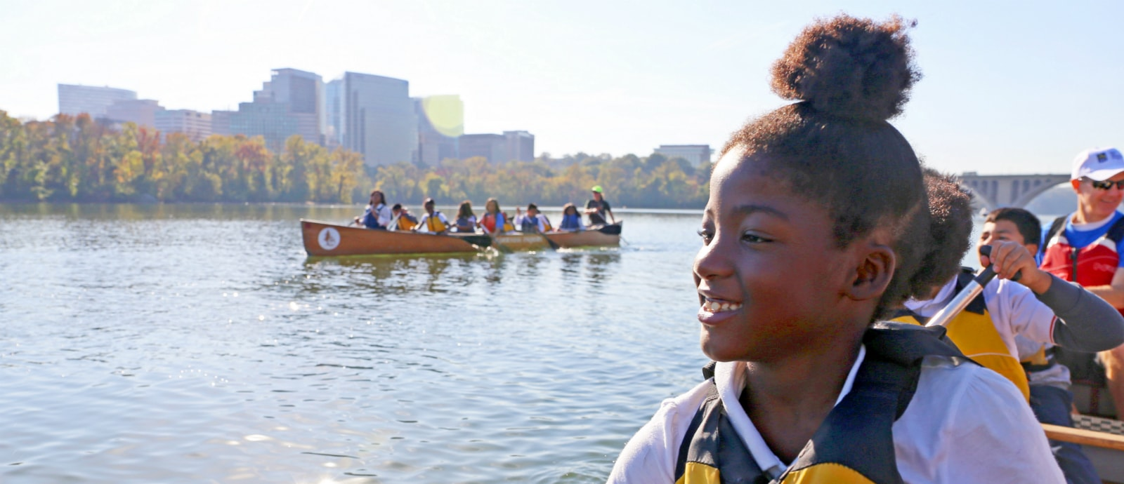 African American girls outdoors in Voyageur Canoe with Canoemobile Program.