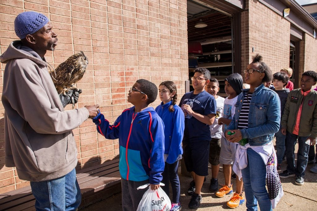 A raptor expert from Earth Conservation Corps lets the children touch an owl.