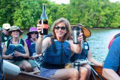 Woman with bottle of wine in canoe