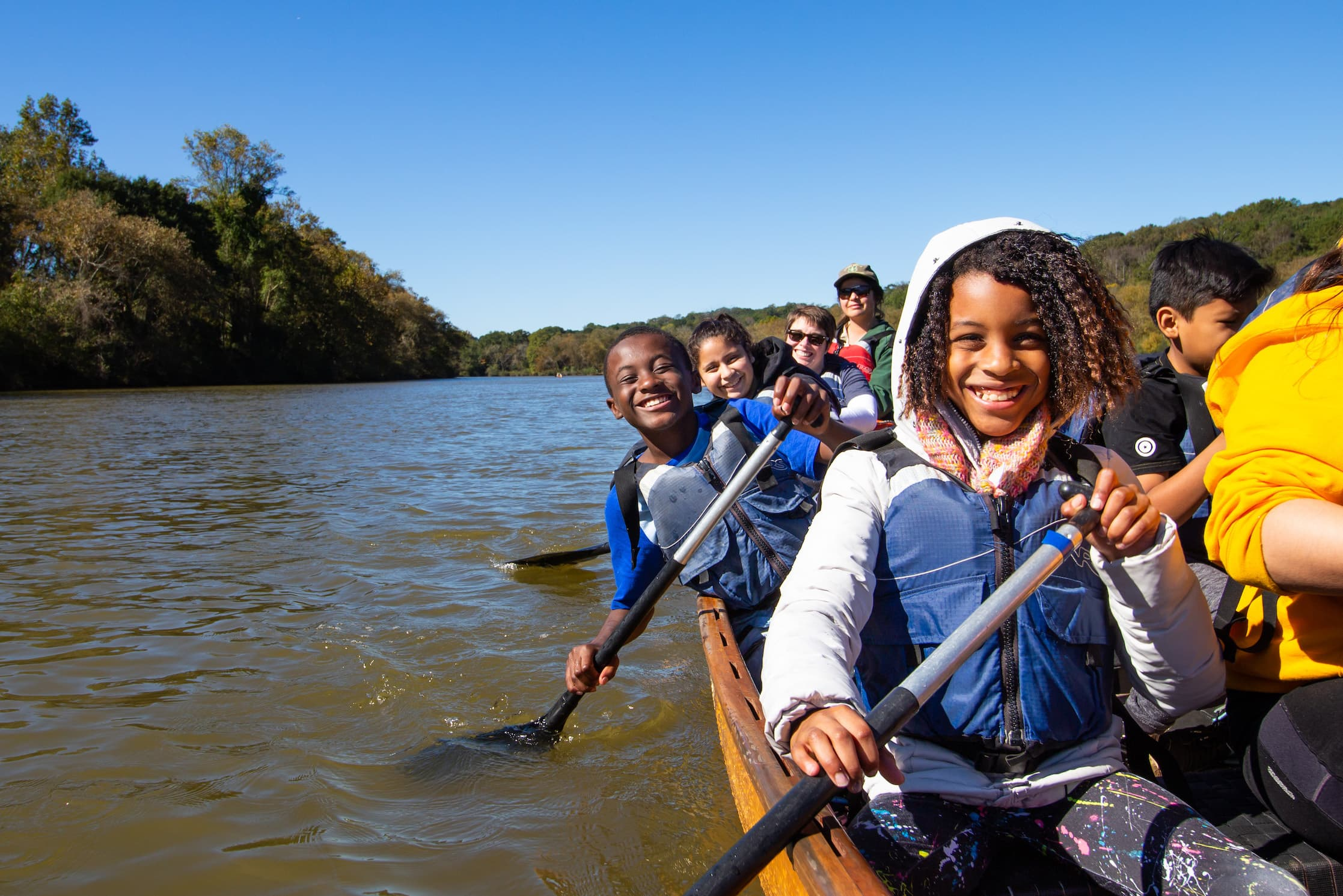 Smiling group of kids canoeing.