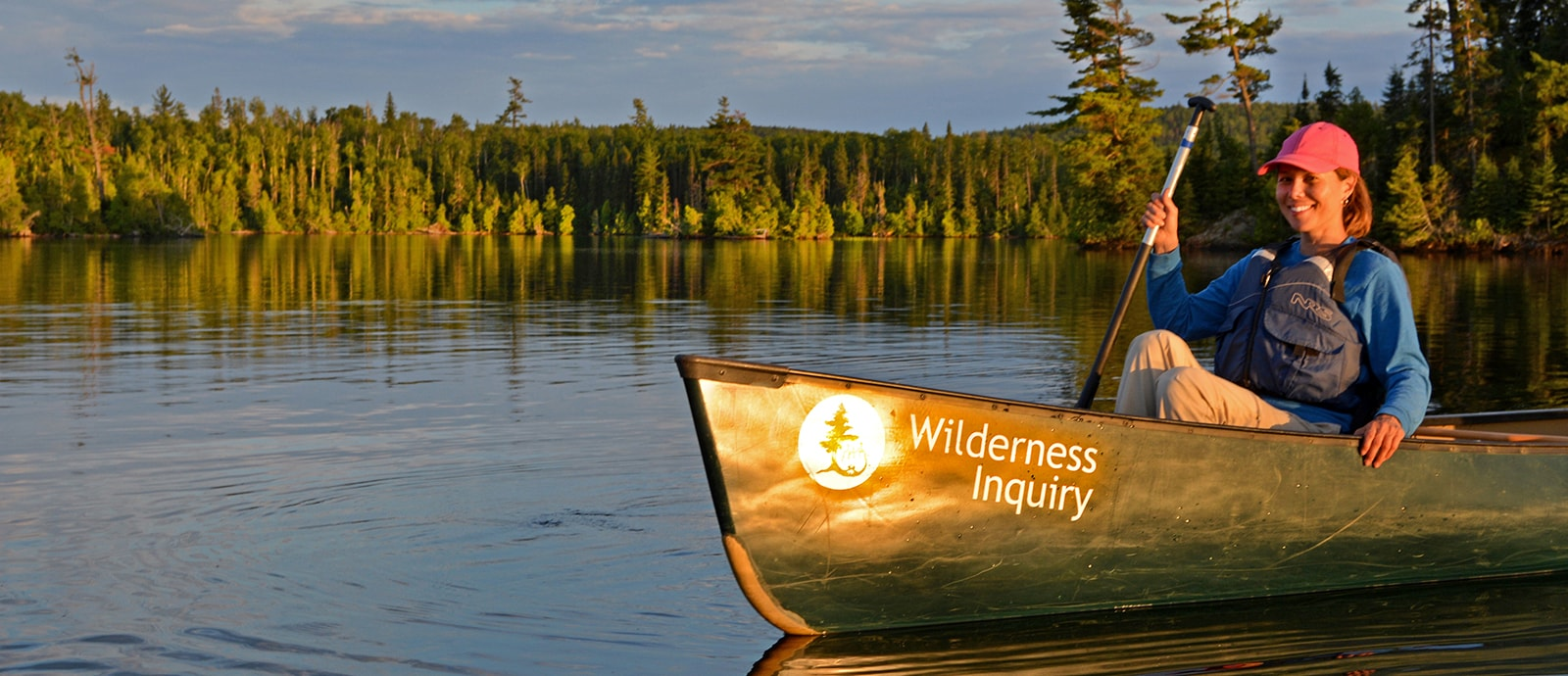 Woman paddling green canoe in the Boundary Waters Canoe Area Wilderness