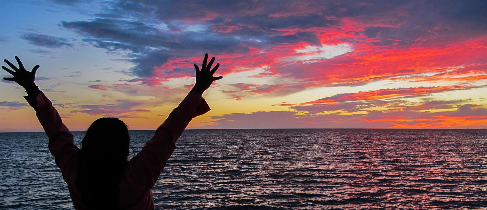 Woman lifts her arms to the sunset