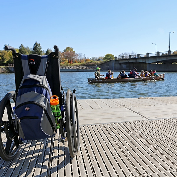Wheelchair in foreground with canoe full of paddlers in background