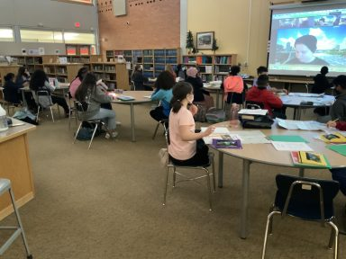 Students sit around circular tables doing activities while a Wilderness Inquiry outdoor leader presents on a projector screen