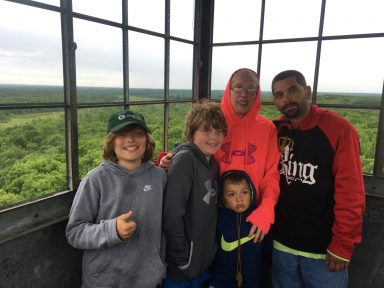 A family of 5 stands at the top of a tower overlooking a green forest
