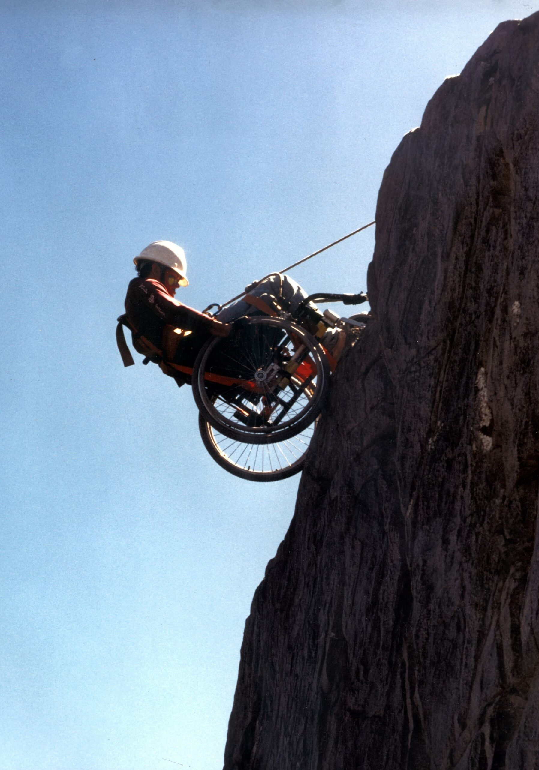 """dangling wheelchair Erin Broadbent. The trip included a day of rappelling down a sheer rock face along the river. Erin's eyes lit up with excitement. Greg Lais describes the scene, """"I was standing in the river at the base of the cliff, watching these two wheelchair rims edge their way over the cliff. Erin was cool as a cucumber, started rolling her way down the sheer cliff face when I took the picture. A moment later, her wheel caught in a crack of rock and she flipped sideways. I looked up at her and asked if she was nervous. She responded, 'Nah, I already broke my neck once, this is no big deal.'"""" Peering at Erin over the cliff, the crowd above burst into applause as Erin freed herself and made her way down the cliff. After Erin, everyone in the group enthusiastically rappelled down the cliff."""