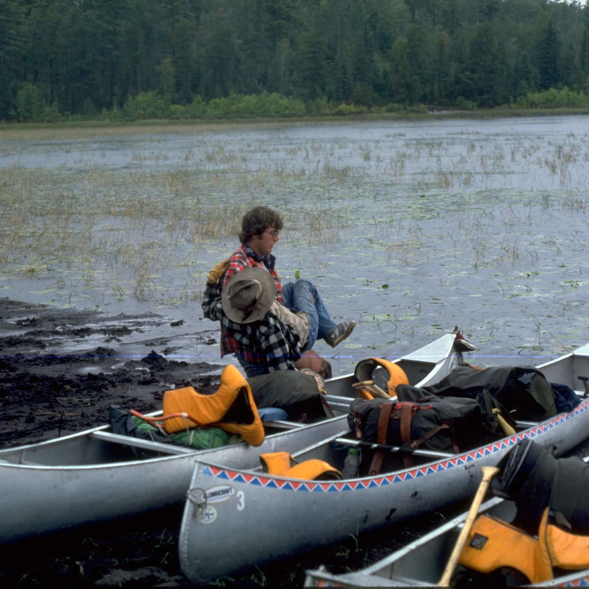 Greg Lais transfers Ted Oftedahl on WI's first trip in 1977. This is the portage into Lac La Croix.